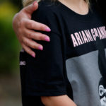 A youngster wearing a t-shirt showing U.S. singer Ariana Grande talks to the media near the Manchester Arena in Manchester