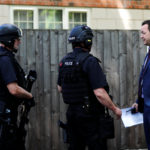 Armed and plain clothes police officers stand outside a residential property near to where a man was arrested in the Chorlton area of Manchester