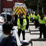 Police officers take part in an operation on a residential street in Manchester