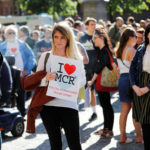 A woman waits to take part in a vigil for the victims of an attack on concert goers at Manchester Arena, in central Manchester