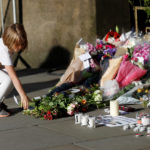 A girl leaves flowers for the victims of an attack on concert goers at Manchester Arena, in central Manchester