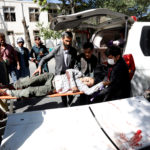 Men move an injured man to a hospital after a blast in Kabul, Afghanistan