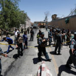 Afghan policemen inspect at the site of a blast in Kabul, Afghanistan