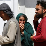 Relatives of Afghan victims mourn outside a hospital after a blast in Kabul, Afghanistan