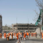 Afghan municipality workers sweep a road outside the German embassy after a blast in Kabul, Afghanistan