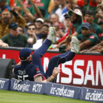 England's Ben Stokes falls over the boundry