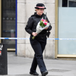 A police woman carries flowers near London Bridge after an attack left 7 people dead and dozens injured in London