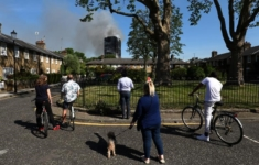 People look at smoke billowing from a tower block severly damaged by a serious fire, in north Kensington, West London
