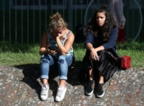 Two women sit on the grass after a tower block was severly damaged by a serious fire, in north Kensington, West London