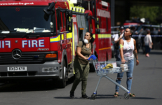 People react near a tower block severely damaged by a serious fire, in north Kensington, West London