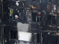 A firefighter examines material in a tower block severely damaged by a serious fire, in north Kensington, West London
