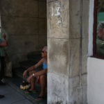 People sit next to a photograph of late Cuban President Fidel Castro in Havana