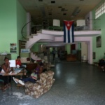 People sit at a government-run office in Havana