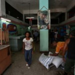 "A woman walks inside a subsidized state store, or ""bodega"", where Cubans can buy basic products with a ration book they receive annually from the government, in Havana"