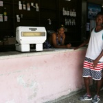 """Young men stand inside a subsidized state store, or """"bodega"""", where Cubans can buy basic products with a ration book they receive annually from the government, in Havana"""