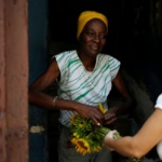 A woman sells flowers from the doorstep of her home in Havana