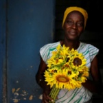 A woman poses for a photograph as she offers flowers for sale from the doorstep of her home in Havana