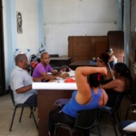 People sit together at an office of the Committee for the Defense of the Revolution (CDR) in Havana