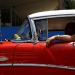 A man drives a vintage car in Havana
