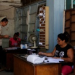 "People are seen at an office that hands out ration books for subsidized state stores, or ""bodegas"", where Cubans can buy basic products they receive annually from the government, in Havana"